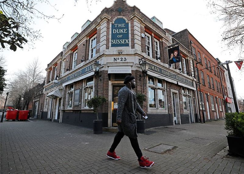 LONDON. A man walks past the Duke of Sussex pub with a sign depicting the image of Britain's Prince Harry and his wife Meghan, near Waterloo station, London, Tuesday, March 9, 2021. (AP)