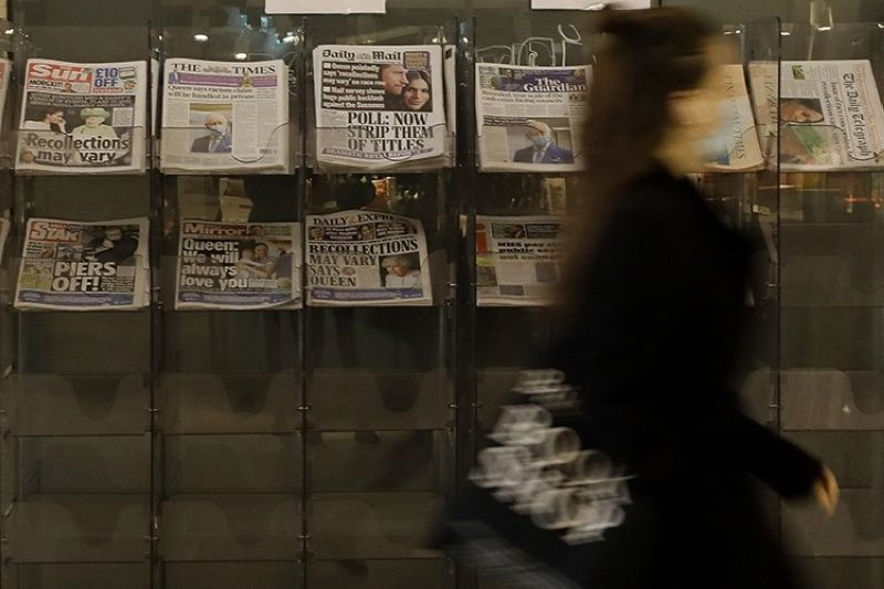 A pedestrian passes newspapers on display with front pages featuring images of members of the royal family, outside a shop in London, Wednesday, March 10, 2021. In countries with historic ties to Britain, allegations by Prince Harry and Meghan about racism within the royal family have raised questions about whether those nations want to be closely connected to Britain anymore after the couple's interview with Oprah Winfrey. (AP Photo)