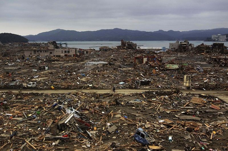 In this March 15, 2011, file photo, a Japanese survivor of an earthquake and tsunami rides his bicycle through the leveled city of Minamisanriku, Miyagi prefecture, northeastern Japan. March 11, 2021 marks the 10th anniversary of the massive earthquake, tsunami and nuclear disaster that struck Japan's northeastern coast. (AP Photo, File)