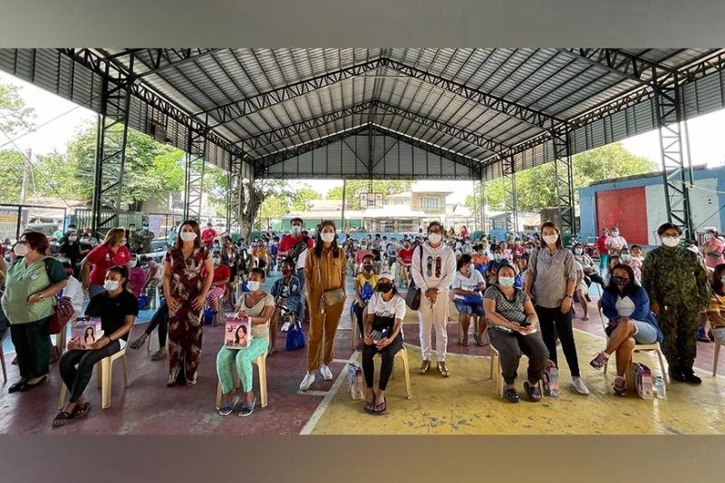 WOMEN POWER. Angeles City Mobile Force Company (ACMFC) Commander Police Lieutenant Colonel Karen Clark, Councilor Jaycee Aguas, fashion designer Mich Viray, make-up artist Shayne Galang, and Police Corporal Aizel Deanne Marie Lopez with the 100 women from Barangay Amsic who benefited from the caravan initiated by the ACMFC on March 12, 2021, in Angeles City. (Charlene A. Cayabyab)