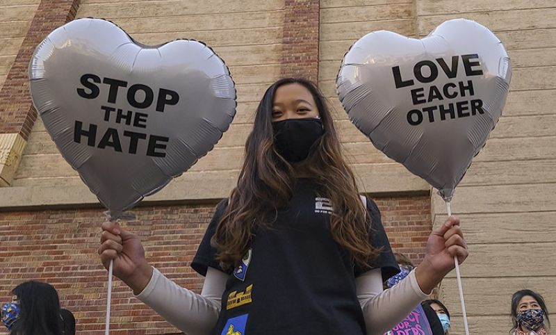 In this March 13, 2021, file photo, Chinese-Japanese American student Kara Chu, 18, holds a pair of heart balloons decorated by herself for the rally