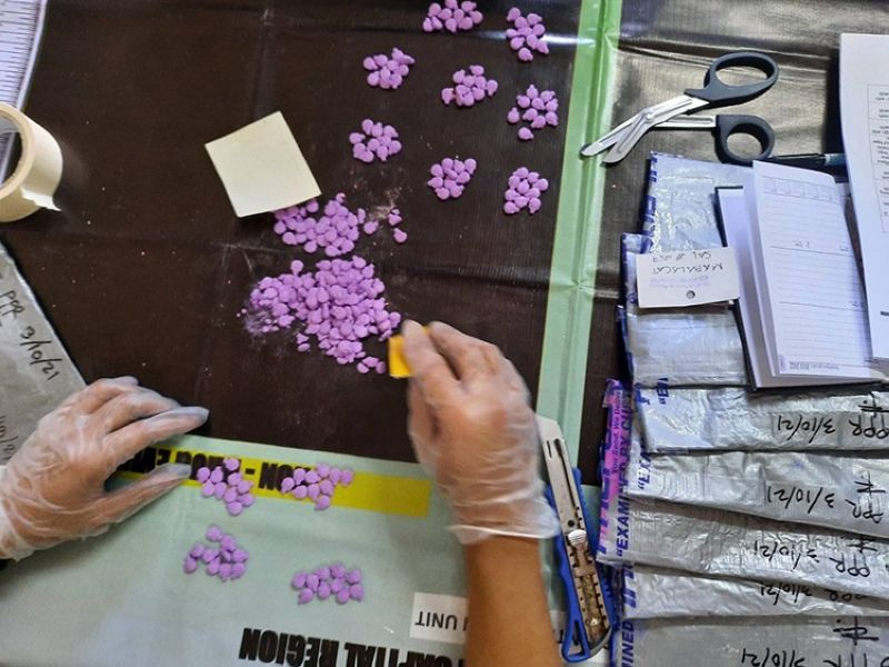 SEIZED IN CONTROLLED DELIVERY. A PDEA agent opens parcels of suspected ecstasy tablets seized in a controlled delivery operation in Mabalacat City on March 18, 2021. (PDEA Central Luzon)