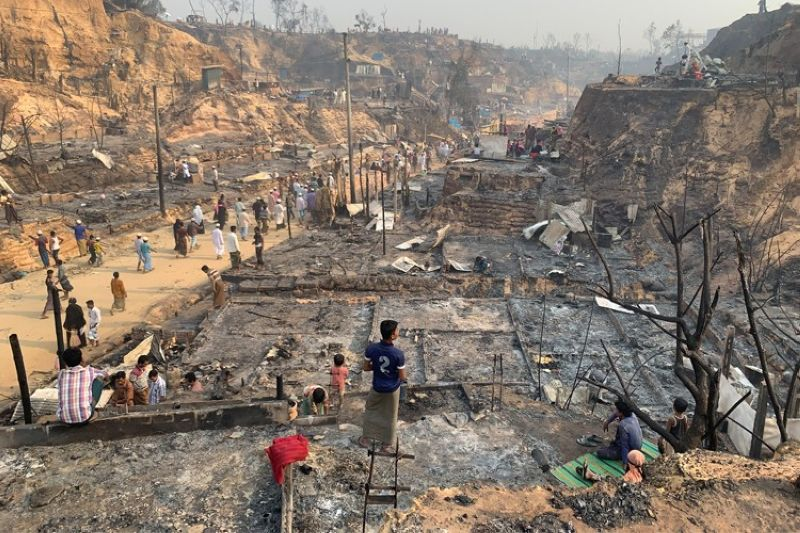 Rohingya refugees stand at the site of Monday's fire at a refugee camp in Balukhali, southern Bangladesh, Tuesday, March 23, 2021. Rescuers recovered more than a dozen charred bodies from a Rohingya refugee camp in southern Bangladesh after a devastating fire that destroyed thousands of shelters, officials said Tuesday. (AP Photo)