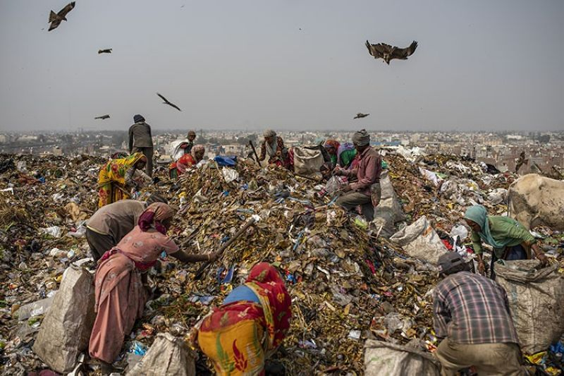 Trash collectors look for recyclables at Bhalswa landfill on the outskirts of New Delhi, India, Wednesday, March 10, 2021. An estimated 20 million people around the world help keep cities clean by scavenging through landfills and dumps. Experts say these trash pickers, who sometimes toil alongside paid municipal sanitation workers, provide a vital service, yet they usually are not on a priority list for vaccines against the coronavirus. (AP Photo)