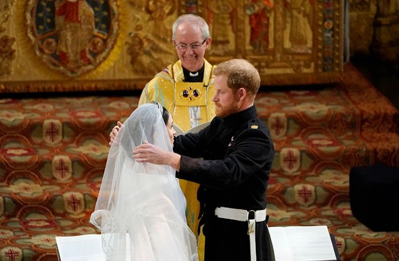 LONDON. In this May 19, 2018 file photo, Britain's Prince Harry pulls back the veil of Meghan Markle watched by Archbishop of Canterbury Justin Welby during their wedding at St. George's Chapel in Windsor Castle in Windsor, near London, England. (AP)