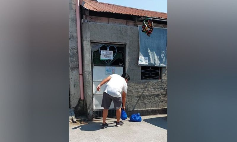 """RELIEF GOODS. A worker from the City Government of San Fernando drops off relief goods at the gate of a residence, as the LGU started extending aid amid the ongoing """"household lockdown."""" (City of San Fernando Information Office)"""
