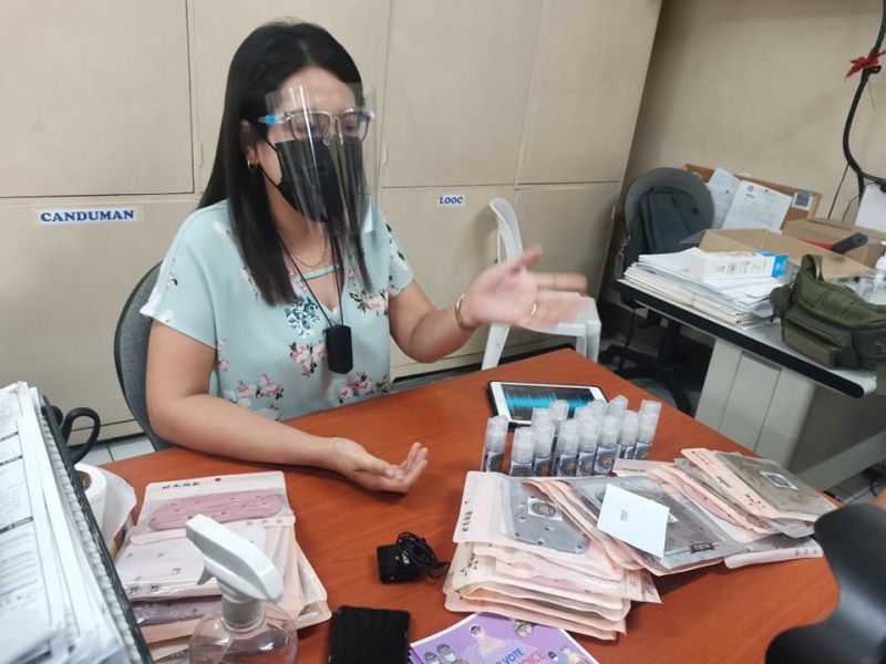 WOMEN POWER. Mandaue City Election Assistant Sarah Cristina Reuyan shows reporters the masks and alcohol that they are giving out to female registrants. Reuyan said from April 6 to 8, they will be giving out masks and alcohol to the first 20 women who will be registering for next year's elections. / Kate Denolang