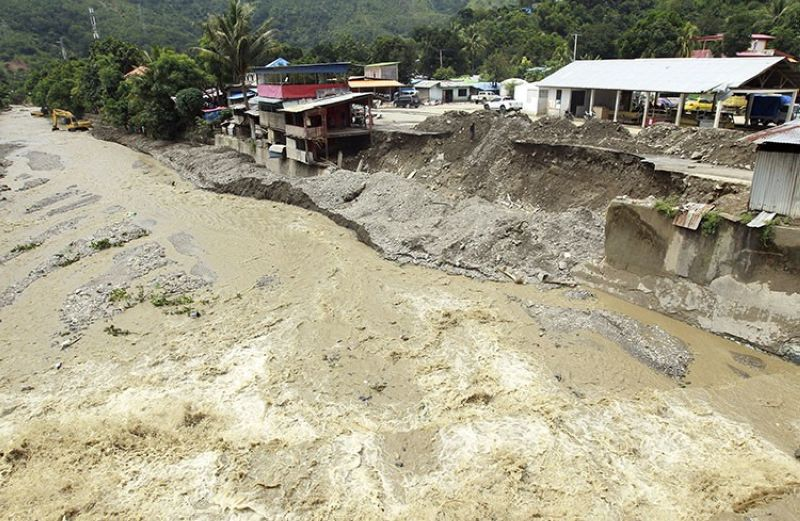 A collapsed retaining wall sits along the banks of a flooded river in Dili, East Timor, Tuesday, April 6, 2021. Several disasters brought on by severe weather in eastern Indonesia and neighboring East Timor have left a number of people dead or missing. (AP Photo)