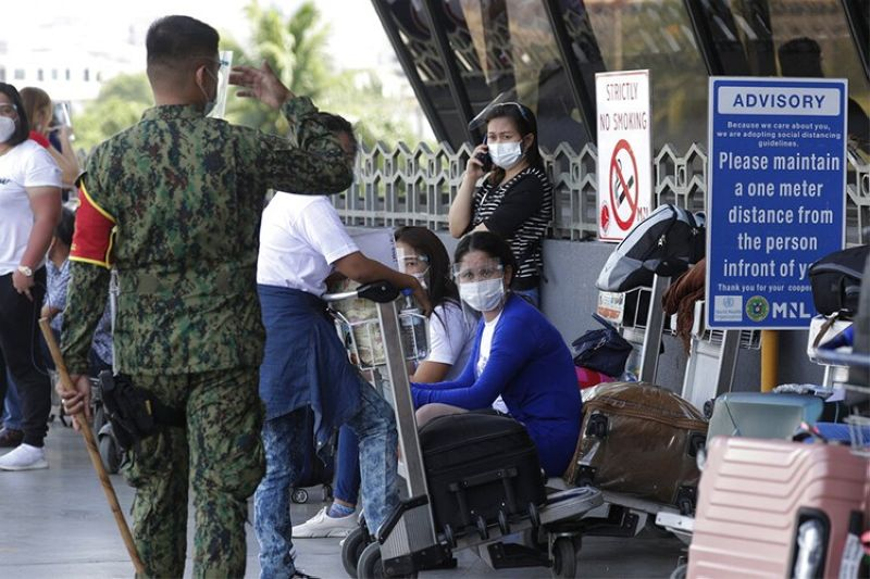 MANILA. A policeman reminds people to practice health protocols at Manila's International Airport on Wednesday, March 17, 2021. (AP)