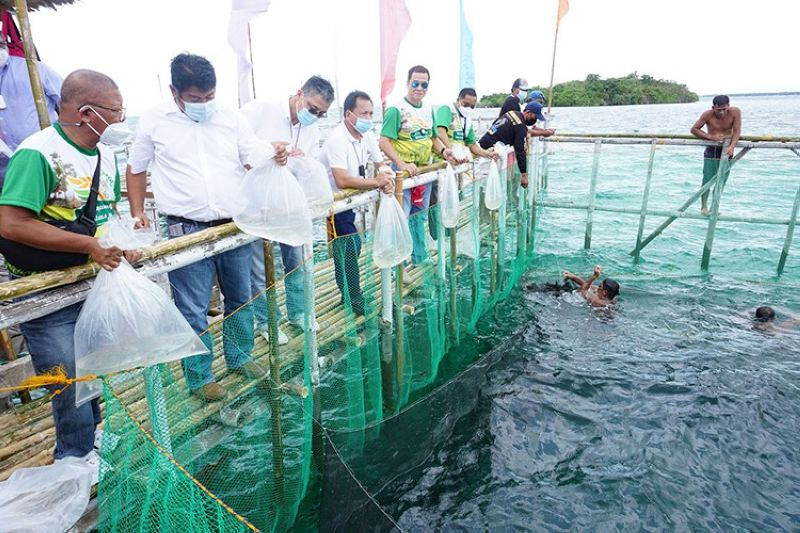 MARINE LIFE. Bantayan Town Mayor Arthur Despi (3rd from left) joins Bureau of Fisheries and Acquatic Resources 7 Director Dr. Allan Poquita (extreme left) and Department of Agriculture 7 Director Salvador Diputado (5th from left) in releasing bangus stocks into Bantayan's marine culture park on Thursday, April 15, 2021. (Alex Badayos)