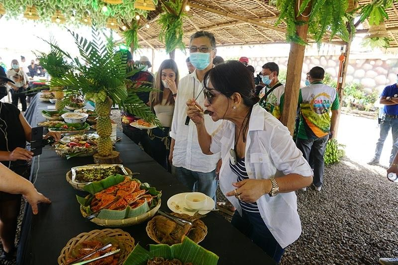 TASTING BANTAYAN. Gov. Gwendolyn Garcia samples one of the dishes on display at the first Bantayan Food Fair in the northern Cebu town as Bantayan Mayor Arthur Despi looks. Despi said the Municipal Government launched the food fair on April 15, 2021 to boost the town's tourism economy amid the coronavirus pandemic. / ALEX BADAYOS