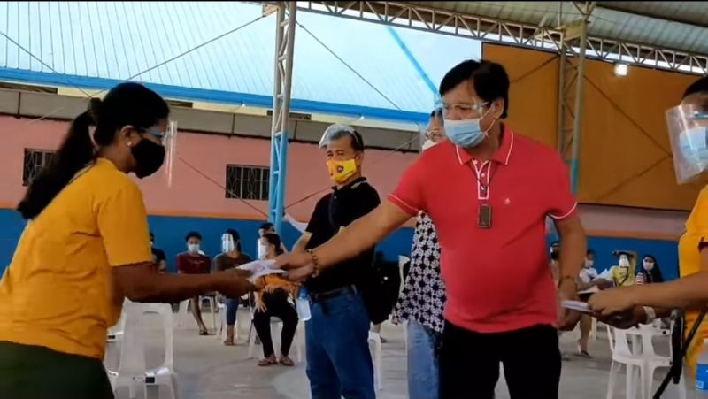 SCHOLARSHIP GRANTS. Mindful of the health protocols, Mayor Abundio Punsalan Jr. hands over financial assistance to a student in Barangay Concepcion, San Simon town. (Contributed photo)
