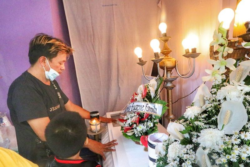 HUSBAND'S GRIEF. Danilo Nepomuceno visits the wake of his wife, Ritchie, in Barangay Quiot on Wednesday, April 21, 2021, two days after Nepomuceno was shot to death by motorcycle-riding assailants. Danilo said Ritchie, 35, had sent him text messages on Monday morning, April 19, hours before the fatal attack in which she had asked if the two of them could mend the cracks in their relationship. / AMPER CAMPAÑA