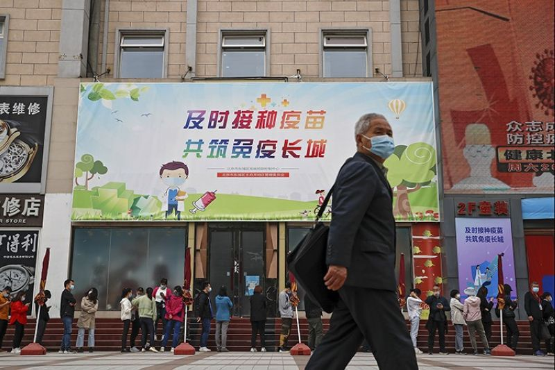 A man wearing a face mask to help curb the spread of the coronavirus walks by masked residents lining up for Covid-19 vaccine at a vaccination site with a board displaying the slogan,
