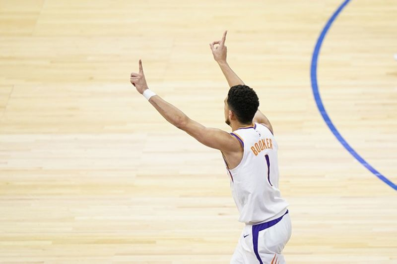 Phoenix Suns' Devin Booker reacts after making a basket during the second half of an NBA basketball game against the Philadelphia 76ers, Wednesday, April 21, 2021, in Philadelphia. (AP Photo)