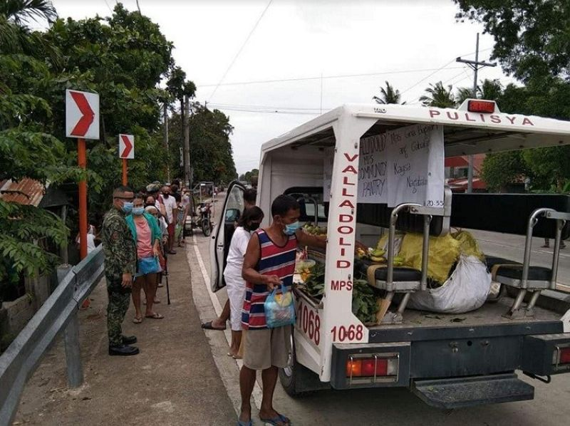VALLADOLID. Residents avail some goods from the mobile community pantry initiated by Valladolid Municipal Police Station Thursday. (Contributed photo)