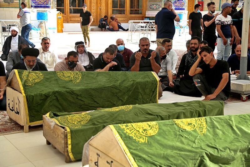 Mourners pray near the coffins of coronavirus patients who were killed in a hospital fire, during their funeral at the Imam Ali shrine in Najaf, Iraq, Sunday, April 25, 2021. Iraq's Interior Ministry said Sunday that over 80 people died and over 100 were injured in a catastrophic fire that broke out in the intensive care unit of a Baghdad hospital tending to severe coronavirus patients in the early morning Sunday. (AP Photo)
