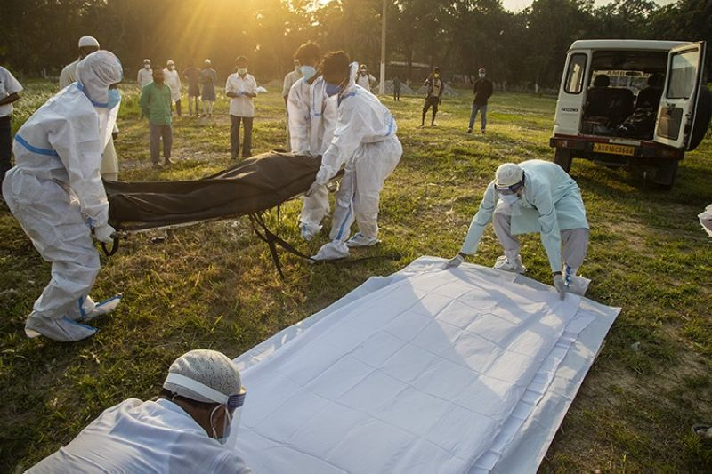 Municipal workers prepare to bury the body of a person who died of Covid-19 in Gauhati, India, Sunday, April 25, 2021. (AP Photo)