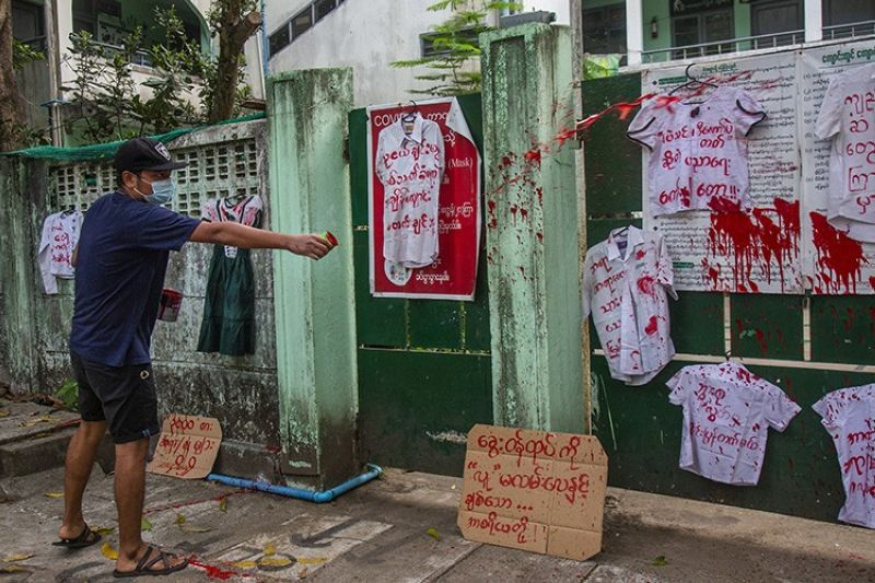 An anti-coup protester splashes red paint on student uniforms after they hanged them outside a school during a demonstration against the re-opening of the school by the junta government at Yangon, Myanmar, Tuesday, April 27, 2021. Demonstrations have continued in many parts of the country since Saturday's meeting of leaders from the Association of Southeast Asian Nations, as have arrests and beatings by security forces despite an apparent agreement by junta leader Senior Gen. Min Aung Hlaing to end the violence. (AP Photo)