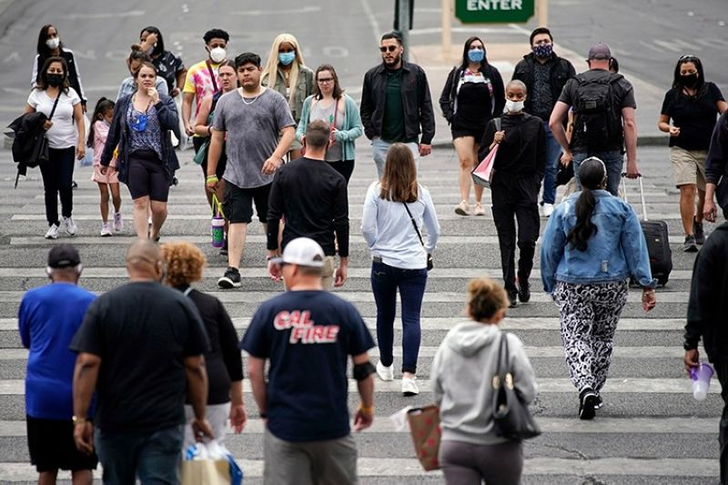 USA. Masked and unmasked pedestrians walk along the Las Vegas Strip Tuesday, April 27, 2021, in Las Vegas. (AP)