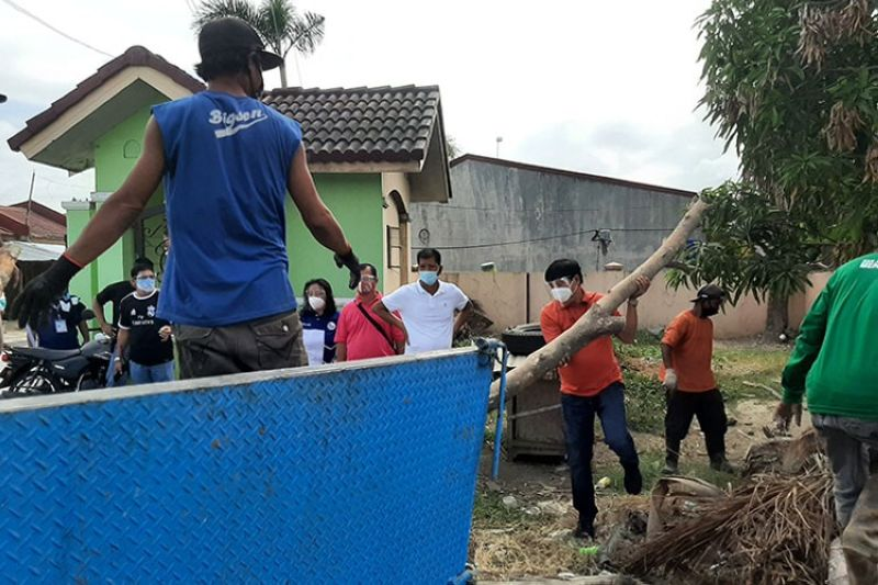 CLEAN-UP DRIVE. Mayor Abundio Punsalan, Jr. led the loading of cut-off branches of trees on the garbage truck during Tuesday's clean-up drive. (Princess Clea Arcellaz)