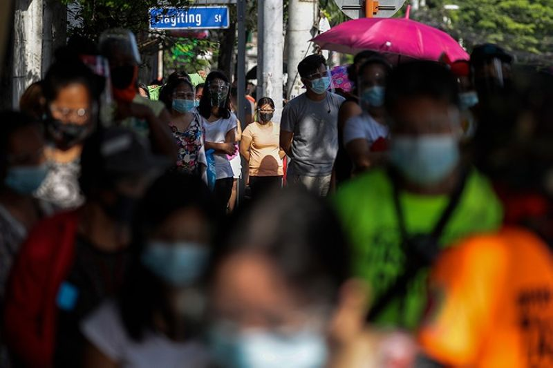 """LOWER GROWTH FORECAST. Residents wearing face masks and face shields queue to get free food at a makeshift stall called """"Community Pantry"""" at Maginhawa Street in Quezon City, Philippines. The Asian Development Bank has revised its economic forecast for the Philippines this year to grow 4.5 percent from the earlier prediction of 6.5 percent in December. (AP)"""