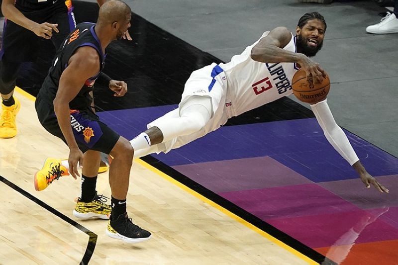 Los Angeles Clippers guard Paul George (13) falls out of bounds after being fouled by Phoenix Suns guard Chris Paul during the second half of an NBA basketball game, Wednesday, April 28, 2021, in Phoenix. (AP Photo)