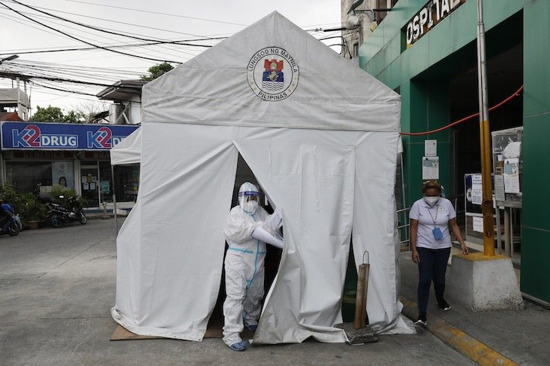 MANILA. A health worker wearing a protective suit goes out of a tent with Covid-19 patients outside a hospital in Manila on April 26, 2021. (AP)