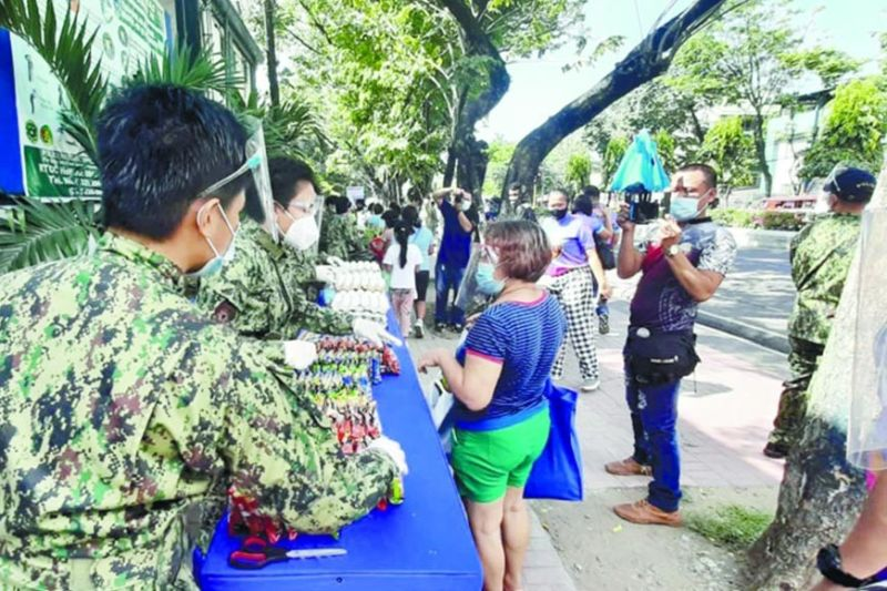 "BARANGAYNIHAN. Personnel of the Police Regional Office 7 hold a ""Barangaynihan"" community pantry in front of their headquarters at Camp Sergio Osmeña in Cebu City on Saturday, May 1, 2021. / Arnold Bustamante"