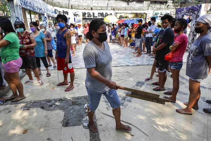 MANILA. A woman holds a piece of wood as she asks other residents to maintain social distancing while queuing for free food supplies at a community pantry in Quezon City on April 29, 2021. (AP)