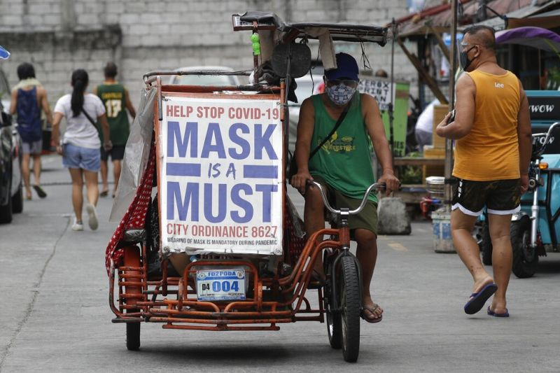 MANILA. A man rides his pedicab with a slogan to remind people to wear masks to prevent the spread of the coronavirus in Manila on April 26, 2021. (AP)