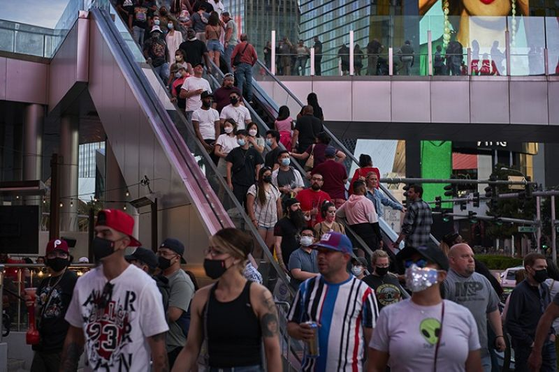 People ride an escalator along the Las Vegas Strip, Saturday, April 24, 2021, in Las Vegas. Las Vegas is bustling again after casino capacity limits were raised Saturday, May 1, to 80% and person-to-person distancing dropped to 3 feet (0.9 meters). (AP Photo)