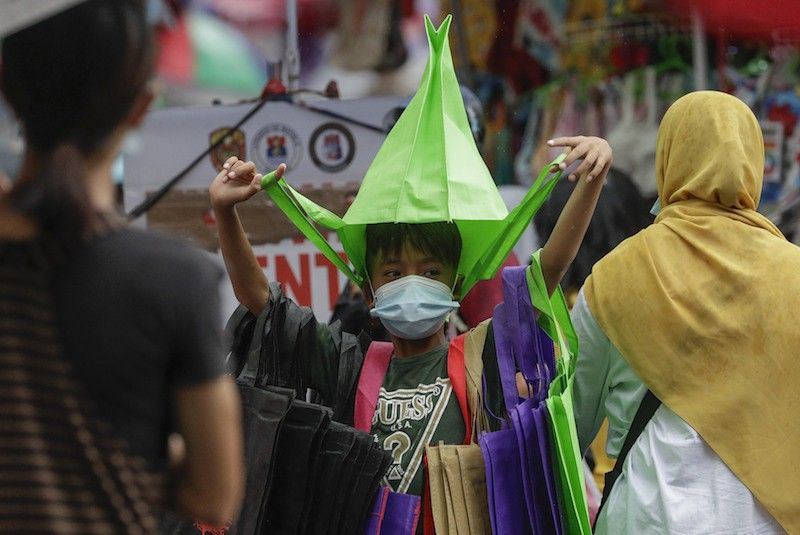 MANILA. In this photo taken in December 2020, a boy wears a face mask as he sells bags in the shopping district of Divisoria in Manila. (File)