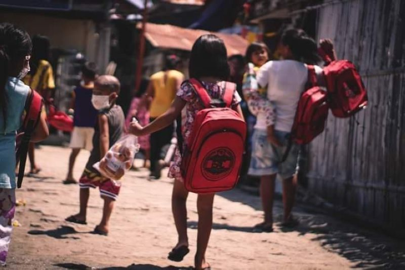 KINDNESS RECEIVED. A girl walks toward her home after receiving a new bag containing school supplies and a plastic bag full of bread during an outreach program of the Skeptron Alumni of Cebu East Branch, an Alpha Kappa Rho alumni group of professionals, in Caubian, Lapu-Lapu City on April 24, 2021. / CONTRIBUTED