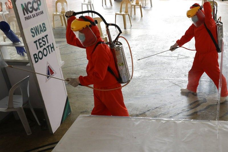 MANILA. Government workers wearing a protective suit disinfect a Covid-19 testing site to curb the spread of the coronavirus in Quezon City, Philippines on Thursday, April 29, 2021. (AP)