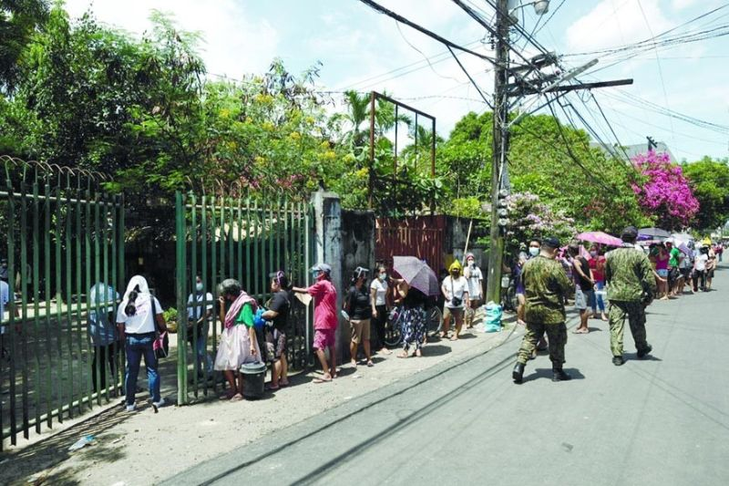 PANTRY CROWD. Police make sure people lining up at the community pantry organized by the St. Joseph the Patriarch Parish in Barangay Mabolo, Cebu City observe minimum health protocols like social distancing. / ALEX BADAYOS