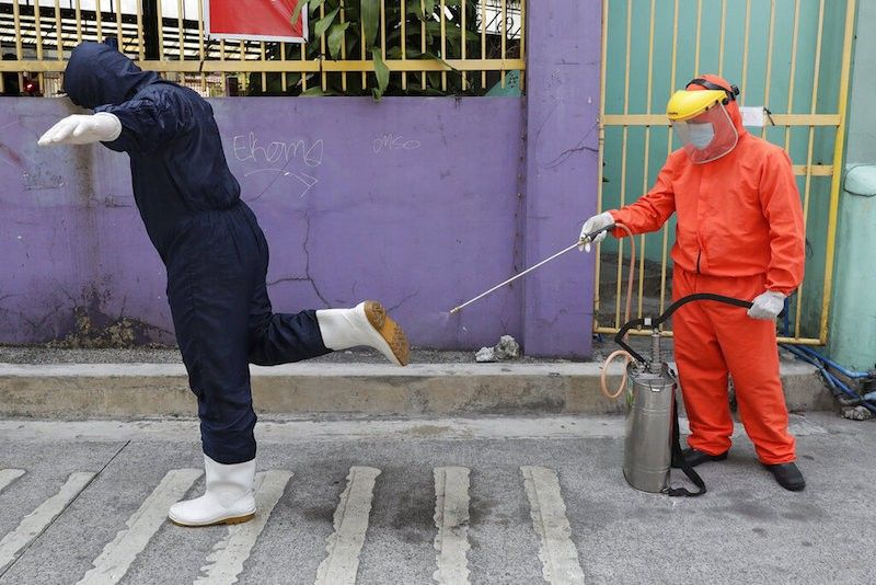MANILA. A government worker wearing a protective suit disinfects the shoes of his colleague outside a Covid-19 testing site to curb the spread of the coronavirus in Quezon City on Thursday, April 29, 2021. (AP)