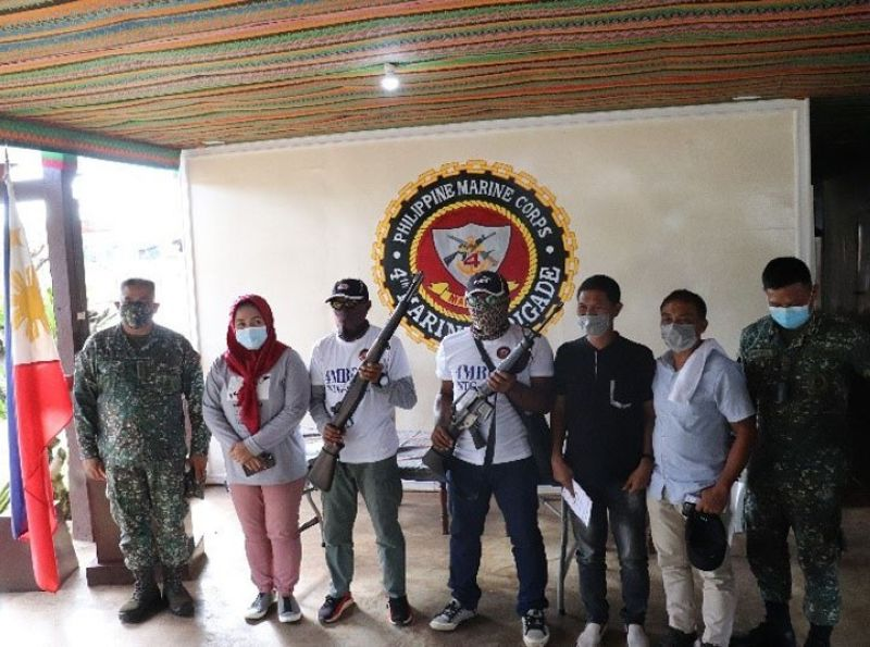 ZAMBOANGA. Two supporters of Abu Sayyaf bandits surrender to government authorities Friday, May 7, in the town of Omar, Sulu. A photo handout shows the two surrenderers (holding rifles) joining military and local government officials in a posterity photo after their surrender. (SunStar Zamboanga)