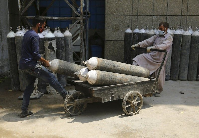 INDIA. Workers carry oxygen cylinders for Covid-19 patients at a government hospital in Jammu, India on May.7, 2021. (AP)
