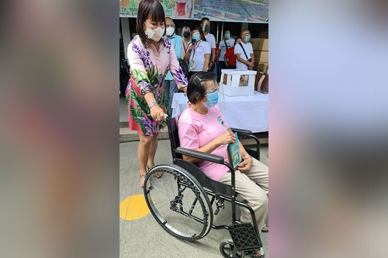 HAPPY MADIR DAY. Provincial Executive Assistance ang Arayat First Lady Madeth Alejandrino awards a wheelchair to a retired barangay health worker during Monday's (May 10, 2021) celebration of Mother's Day and her birthday at the Municipal town hall. She donated 100 wheelchairs to PWDs and senior citizens in the 30 barangays. (Chris Navarro)