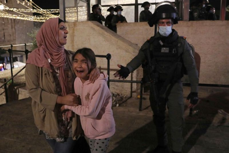 An Israeli police officer gestures to a Palestinian woman and her daughter, frightened by clashes outside of the Damascus Gate to the Old City of Jerusalem Tuesday, May 11, 2021. A confrontation between Israel and Hamas sparked by weeks of tensions in contested Jerusalem escalated Tuesday as Israel unleashed new airstrikes on Gaza while militants barraged Israel with hundreds of rockets. (AP Photo)