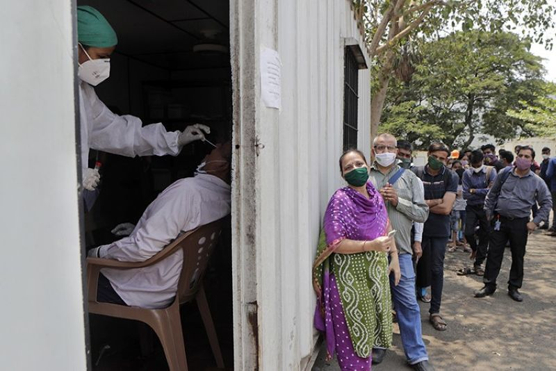 In this May 6, 2021, file photo, a health worker takes a nasal swab sample of a person to test for Covid-19 as others wait for their turn outside a field hospital in Mumbai, India. The World Health Organization said Monday, May 10, that a worrisome variant was first detected in India may spread more easily. Scientists are still tryingto figure out if it resulted in the terrifying surge of infections in the nation, and looking to see if this could this happen elsewhere. (AP Photo, File)