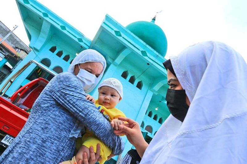 CELEBRATING. Lapu-Lapu City Barangay Pajo Councilor Jasmine Chan (right) greets baby Mu'min Ibn Zubair Tago as she joins the Muslims at the Islam Masjid Lacima Mosque in Pajo in celebrating Eid al-Fitr, the end of Ramadan, on May 13, 2021. (ALAN TANGCAWAN)