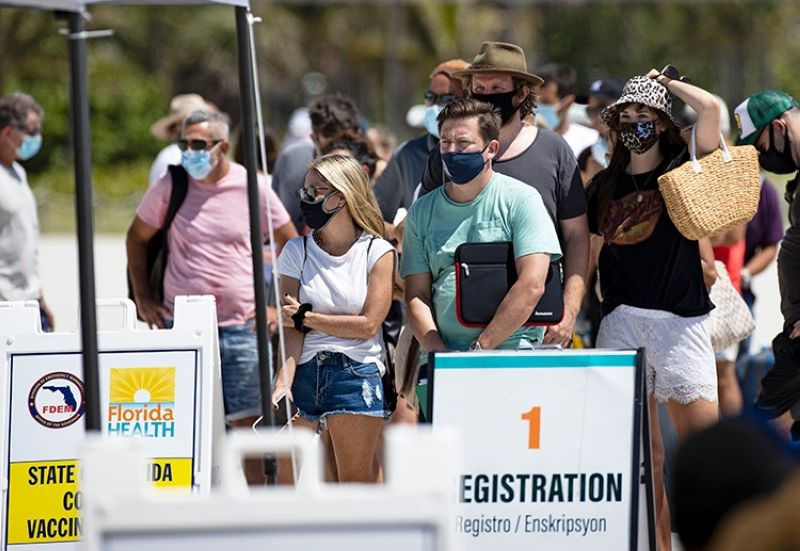 USA. In this May 2, 2021, file photo, people line up to receive a Johnson & Johnson vaccine at the one-time pop-up vaccination site located 16th Street beach on the sand in Miami Beach. (AP)