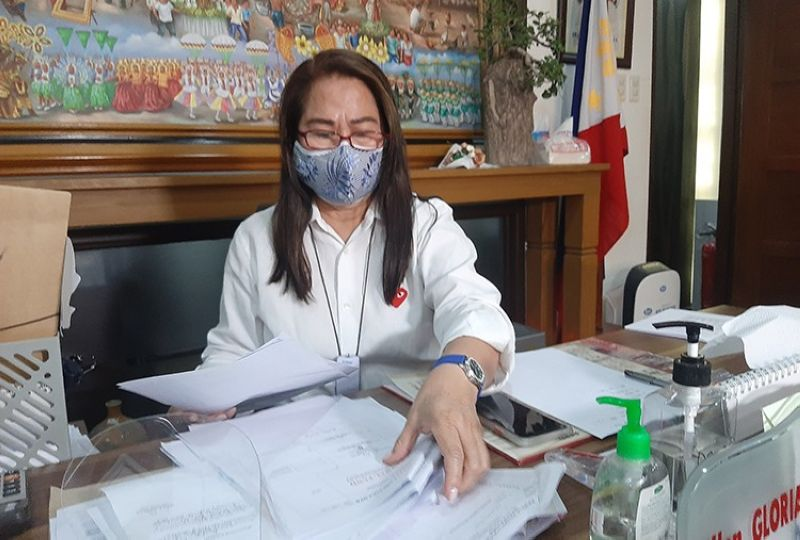BUSY DAY. Mayor Gloria Ronquillo attends to some documents during a busy day in the municipal hall. (Princess Clea Arcellaz)