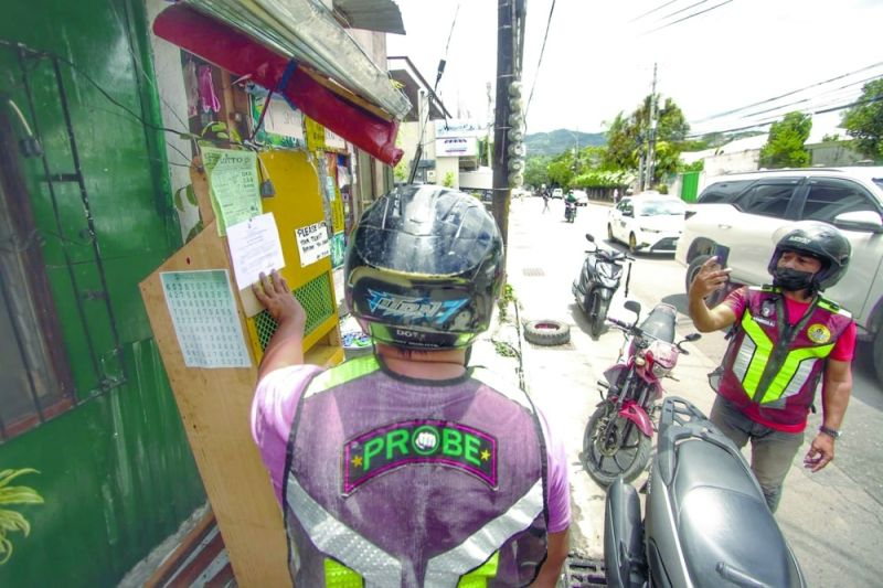 DEMOLITION NOTICE. A Probe member takes a photo of the notice his colleague pinned on an illegal STL outlet in Barangay Guadalupe, Cebu City. The Probe team will start the demolition of all illegal STL outlets in the city on Monday, May 17, 2021. / AMPER CAMPAÑA