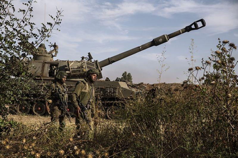 Two Israeli soldiers walk around an artillery unit, at the Israeli Gaza border, Sunday, May 16, 2021. (AP Photo)