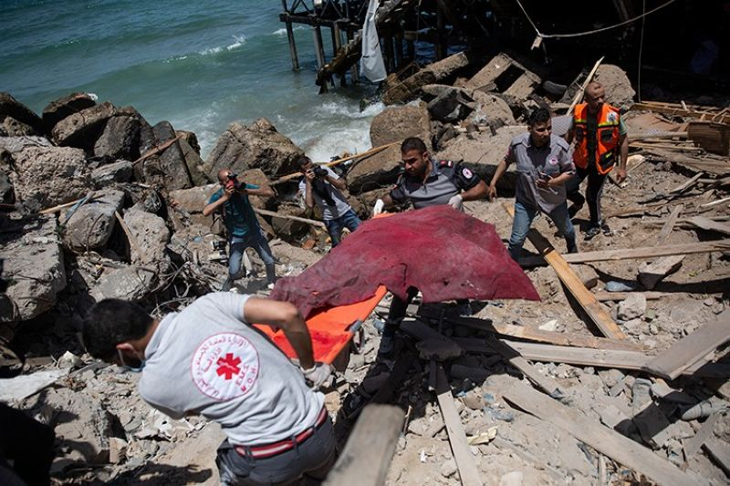 GAZA CITY. Palestinian rescue workers carry the remains of a man found next to a beachside cafe after it was hit by an Israeli airstrike in Gaza City, Monday, May 17, 2021. (AP)