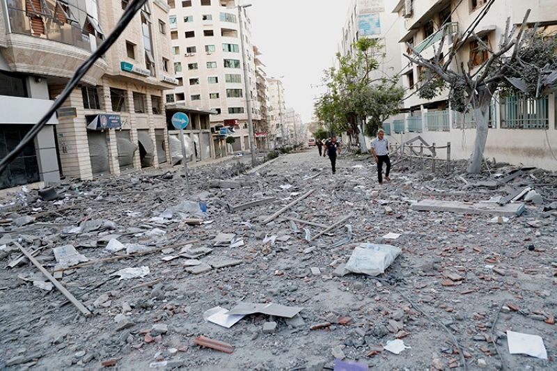 GAZA. In this May 17, 2021, file photo, people inspect the rubble of a destroyed commercial building and Gaza health care clinic following an Israeli airstrike on the upper floors of a commercial building near the Health Ministry in Gaza City. (AP)