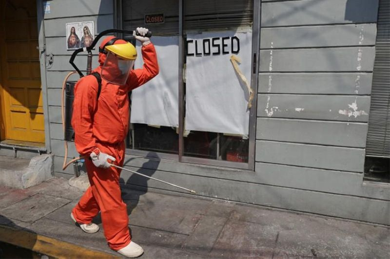 MANILA. A government worker wearing a protective suit walks past a shop that displays a